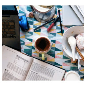 Book, tea cup, bowl and laptop on a table
