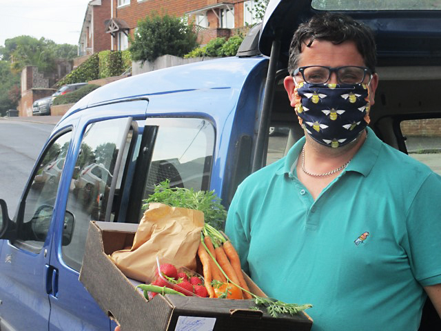 Dan the Grocer with a box of veg