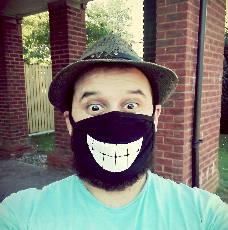 Khaled Wakkaa wearing a smile mask outside