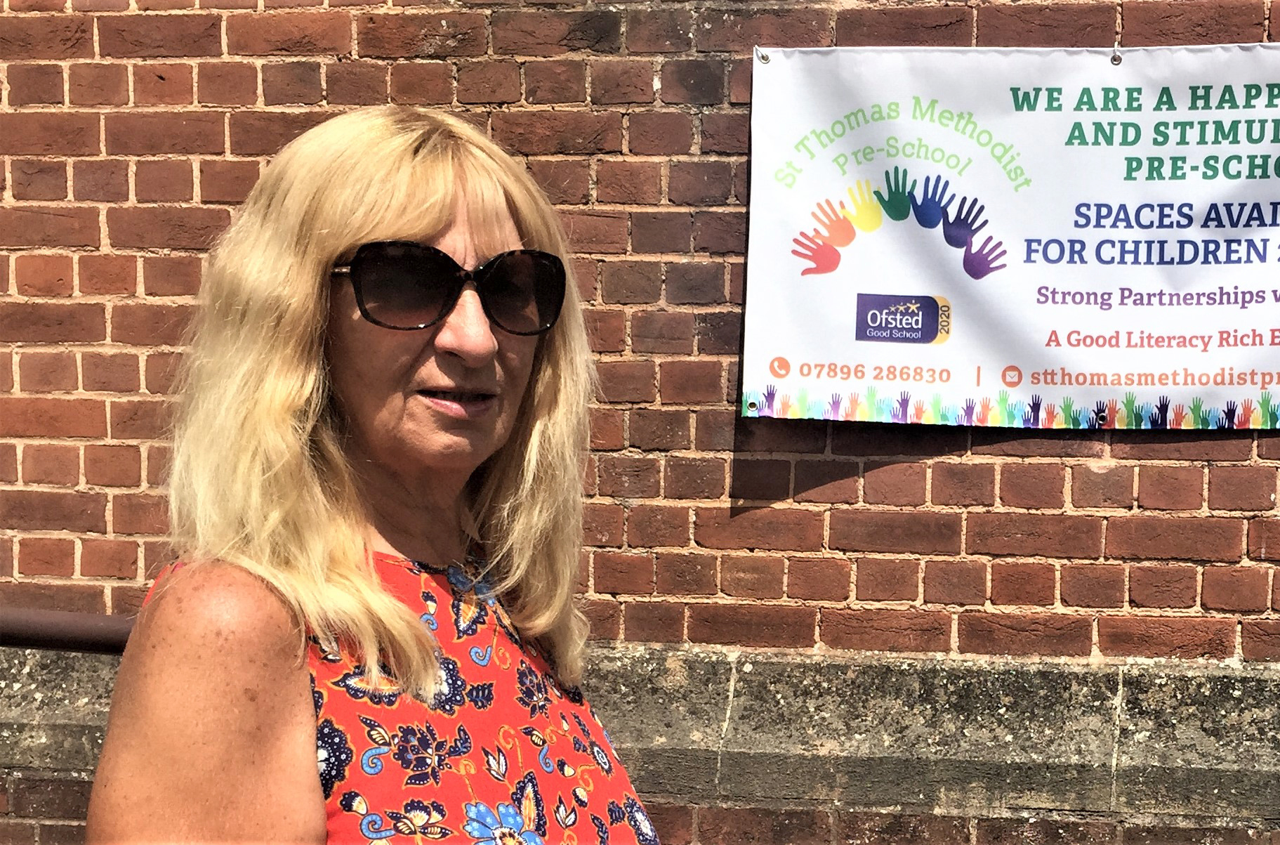 Lesley Albrow in front of a banner